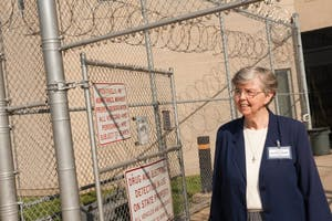 Sister Mary Elizabeth Killoran standing in front of Howard R. Young Prison.