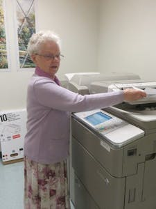 Sr. Angela copies information, prepared individual folders for a bulk mailing, and stacks the collated packets awaiting postage.