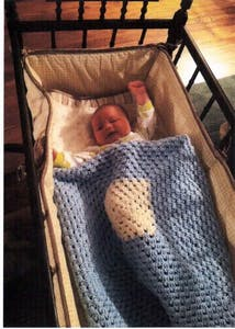 A medical center newborn enjoys the comforts of one of Sr. Ann's hand-crocheted blankets.